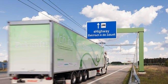Beim Folgeprojekt ENUBA 2 ging Siemens eine Partnerschaft mit der schwedischen Firma Scania ein. Im Fokus steht die optimierte Integration der Antriebstechnik und Stromabnehmer in das Fahrzeug sowie die Bereitstellung der erforderlichen Verkehrssteuerungssysteme. Das Bild zeigt eine Fahrszene auf der erweiterteren eHighway Teststrecke in Groß Dölln.  In the follow-up project, ENUBA 2, Siemens entered into a partnership with Scania, a Swedish company. The focus is on optimizing the integration of the drive system and pantograph into the vehicle and on providing the necessary traffic control systems. The picture shows an driving scene at the extended eHighway test track in Groß Dölln, Germany