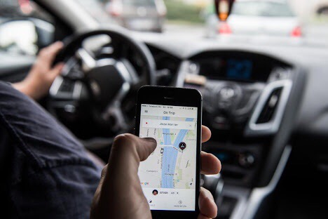 A passenger holds an Apple Inc. iPhone displaying the Uber Technologies Inc. car service taxi application (app) journey progress screen in this arranged photograph in Budapest, Hungary, on Wednesday, July 13, 2016. Uber will suspend its ride-hailing services in Hungary from July 24 following a government decision to pass a bill that allows authorities to block access to the mobile application and fine media promoting it. Photographer: Akos Stiller/Bloomberg via Getty Images